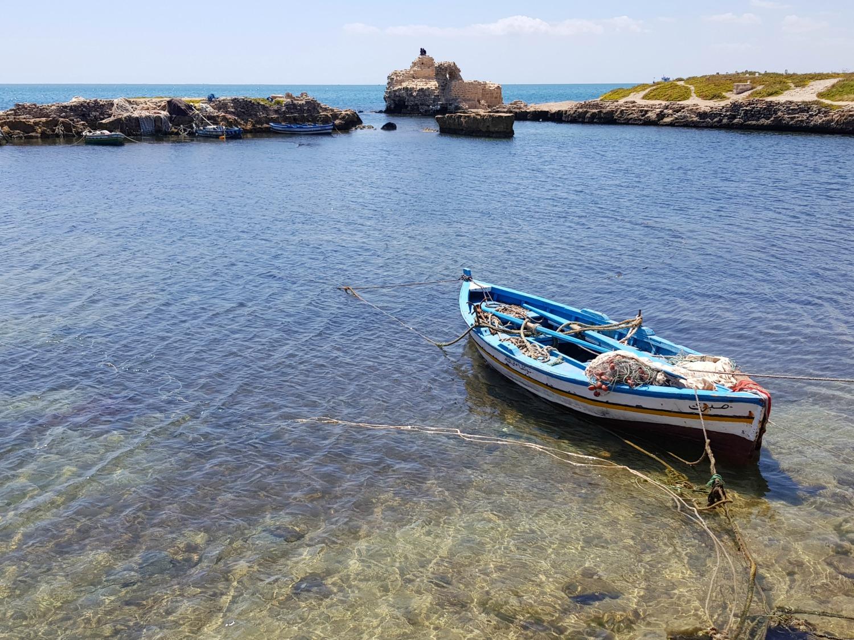 Голубая рыбацкая лодка на чистой воде возле Махдии